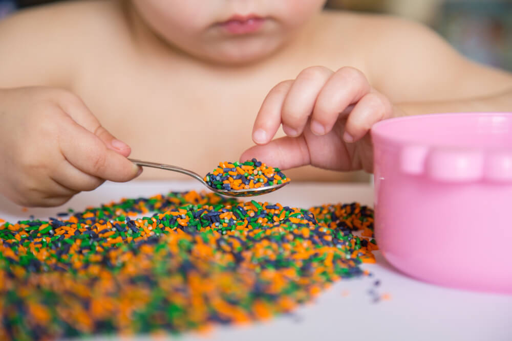 baby playing with colored rice