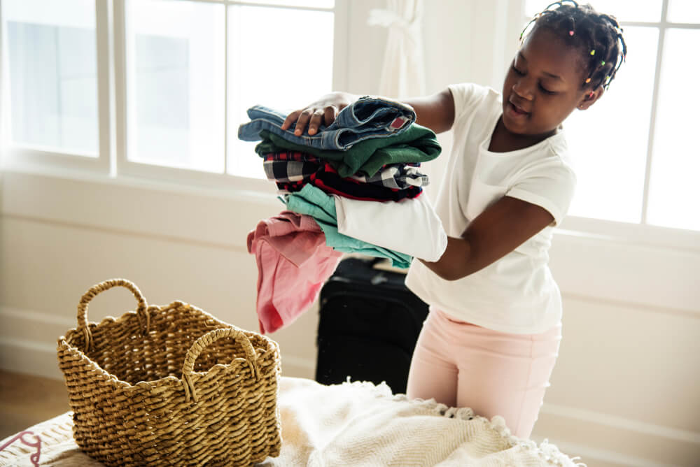 young girl folding her clothes