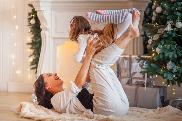 mom plays with her daughter near the Christmas tree home