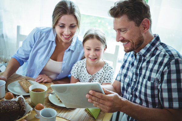 Family using digital tablet while having breakfast at home