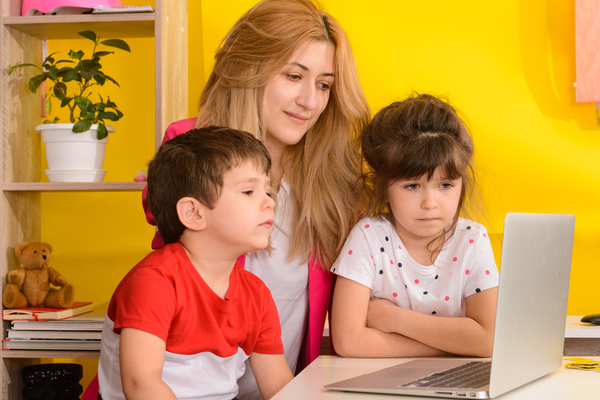 Remote education. Online lessons for children. Homeschooling and distance education for kids. Child student study remotely online with video call teacher. Mom helps kids learn.