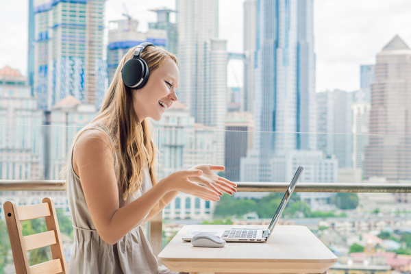 Young woman teaches a foreign language or learns a foreign language on the Internet on her balcony against the backdrop of a big city. Online language school lifestyle.  E