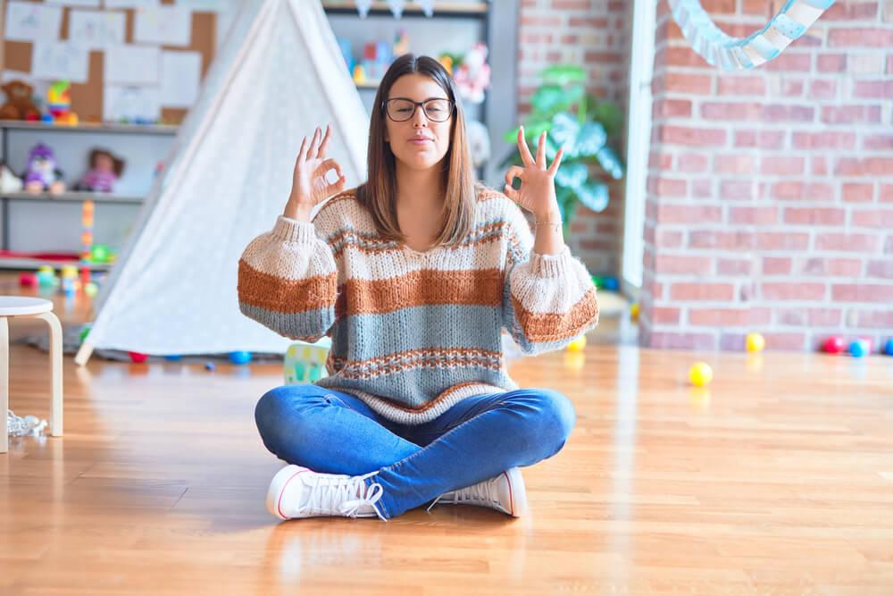 stress management for teachers - relaxed teacher squatting on wooden floor