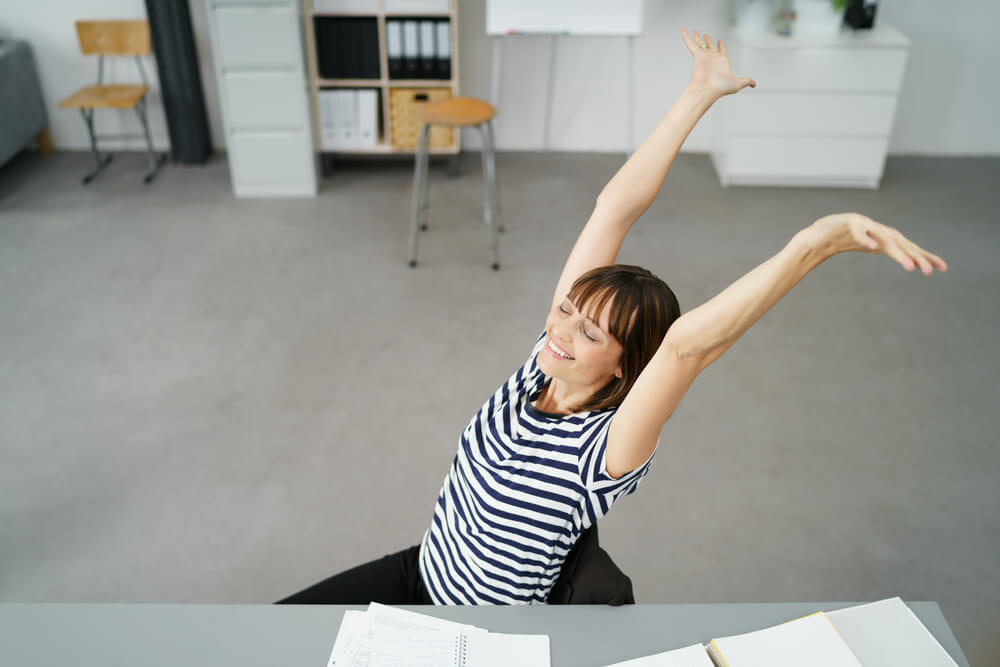 stress management for teachers - young female teacher throwing her hands up in the air