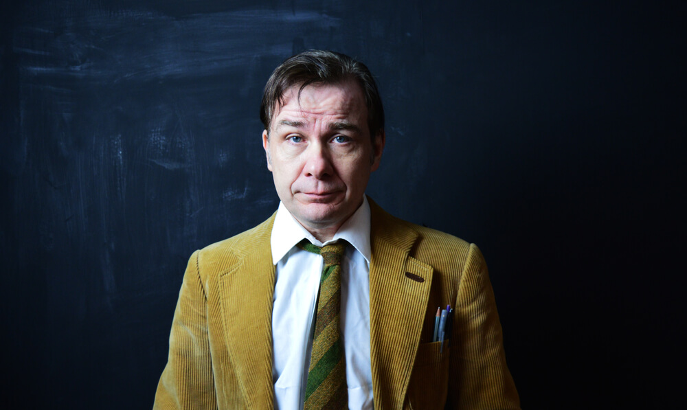 stressed male teacher wearing brown suit