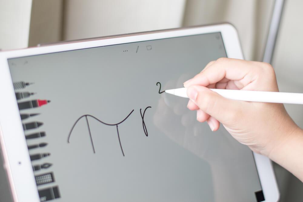 kid writing math symbol on iPad - best algebra apps