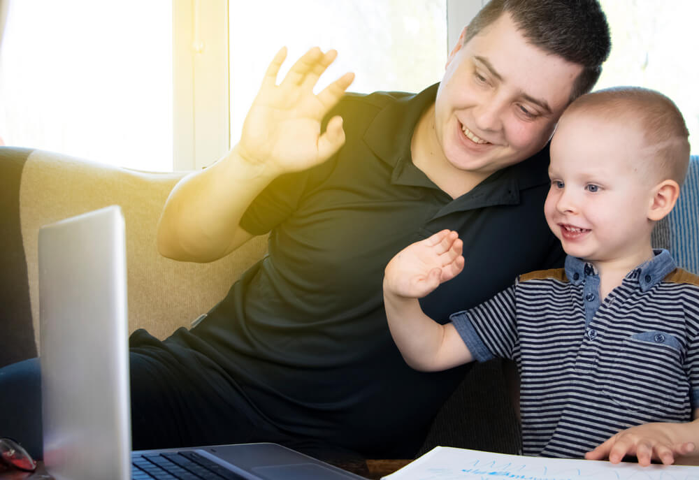 dad and son waving at laptop - teaching children with autism online