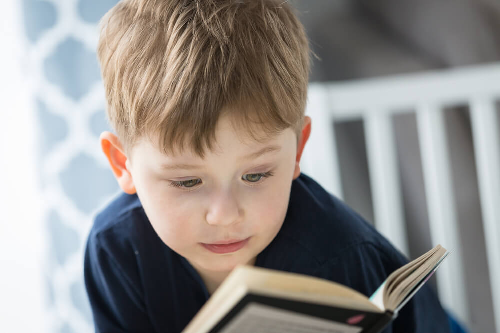 engaging toddlers to read - a young boy reading a book