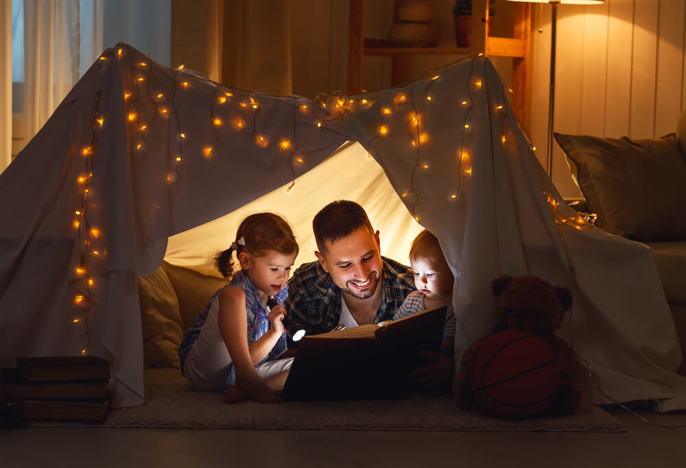engaging toddlers to read - father reading with his children under a fort