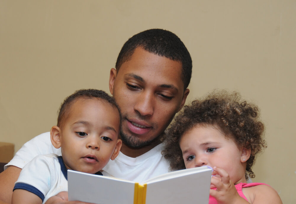 engaging toddlers to read - father reading with his toddler son and daughter