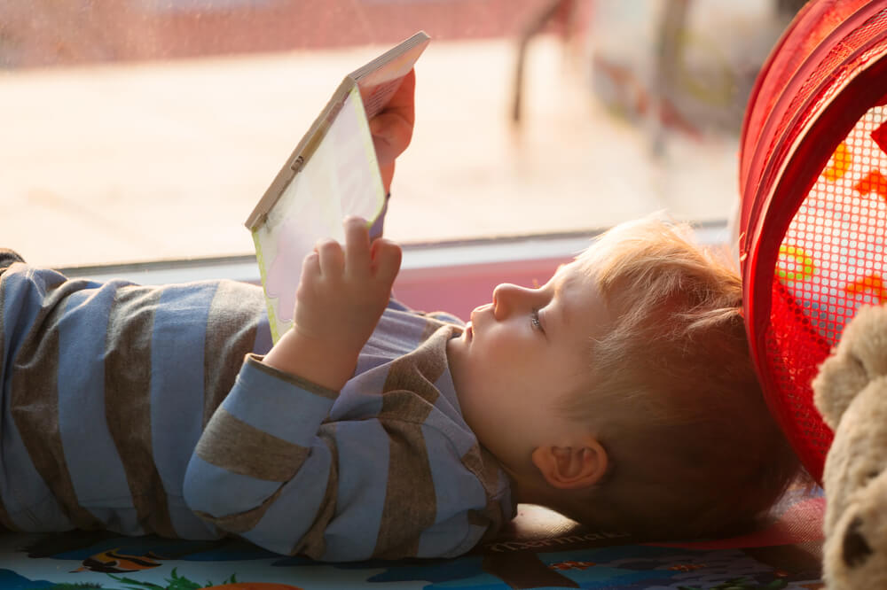 engaging toddlers to read - little boy reading a book while lying down