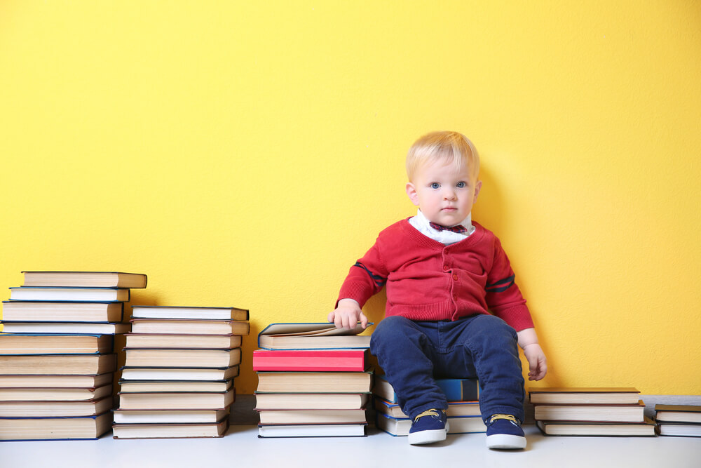 engaging toddlers to read - toddler surrounded by many books