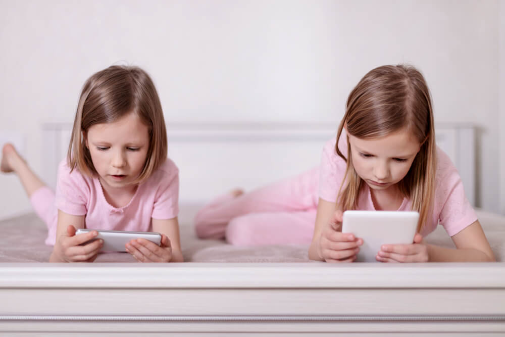 engaging toddlers to read - two young girls each reading on their gadgets