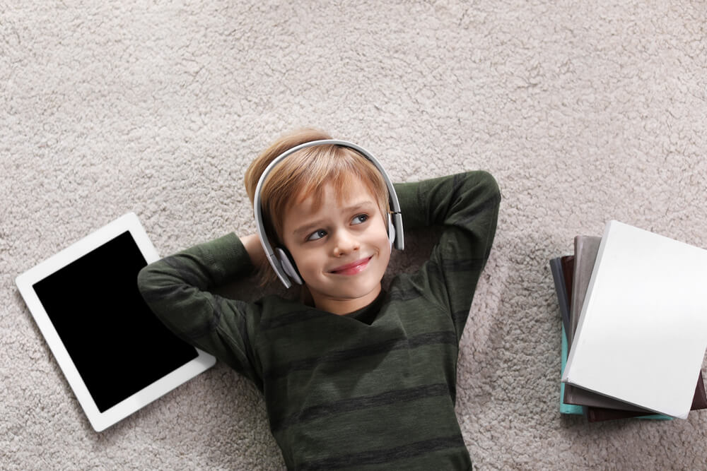 little boy listening to audiobook while lying on the floor