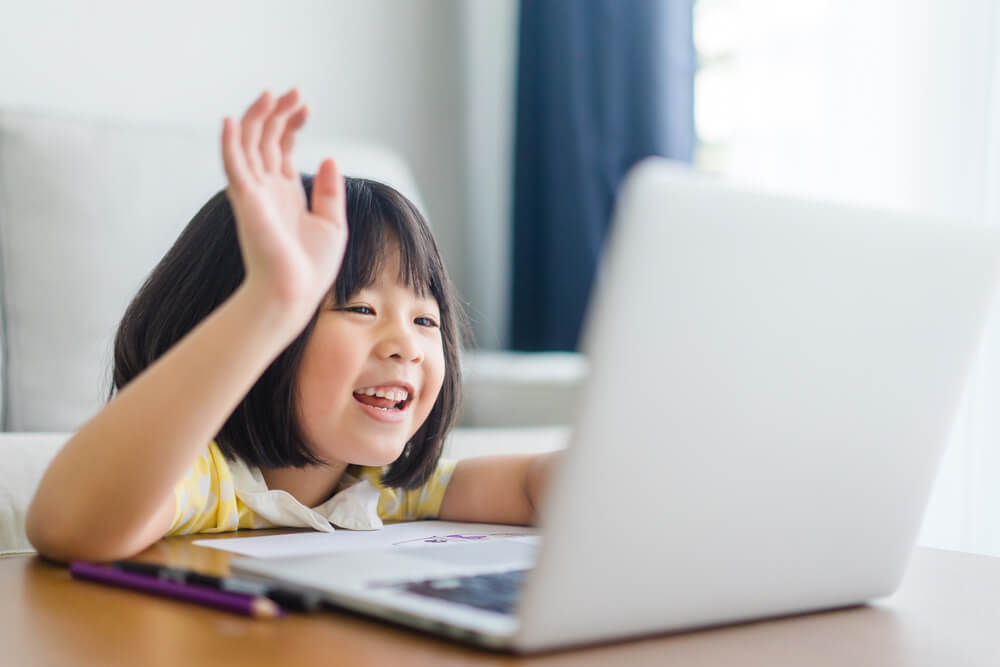 little girl waving to white laptop - teaching children with autism online