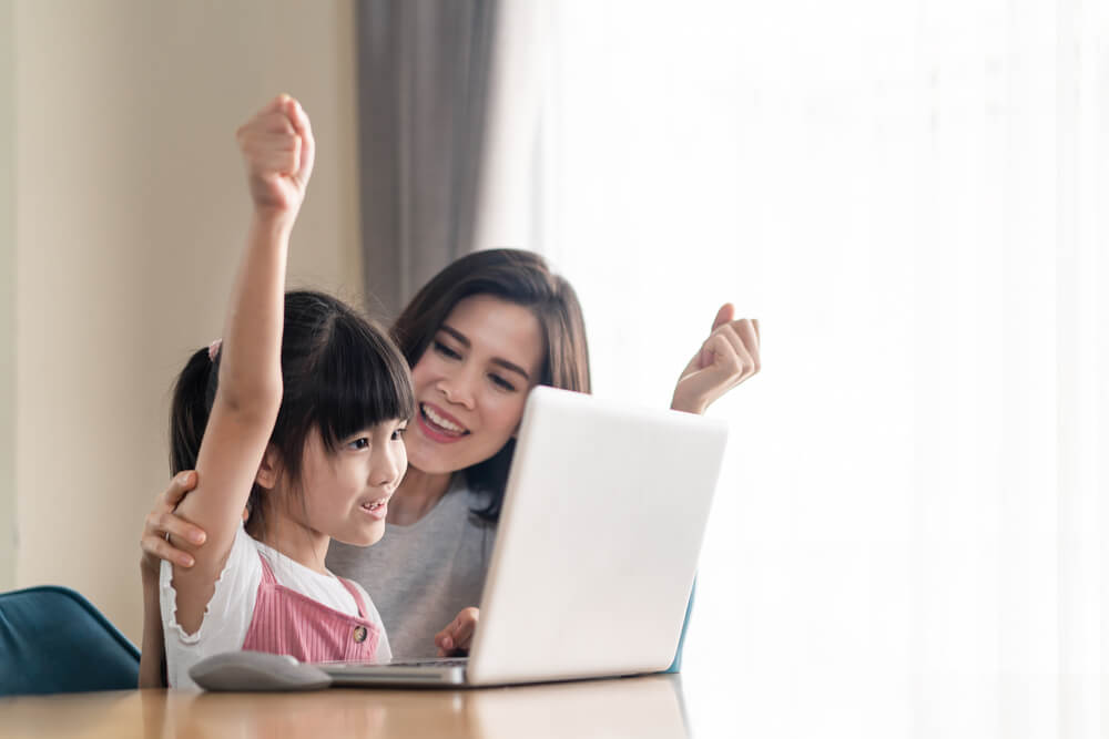 mom and little daughter in front of a laptop, giggling - teaching children with autism online