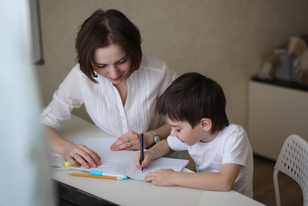 mom teaching his son an activity on white table