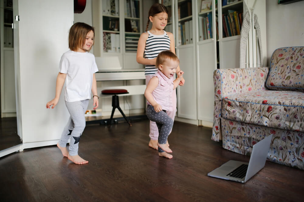 three kids exercising in front of a laptop at a living room - teaching children with autism online