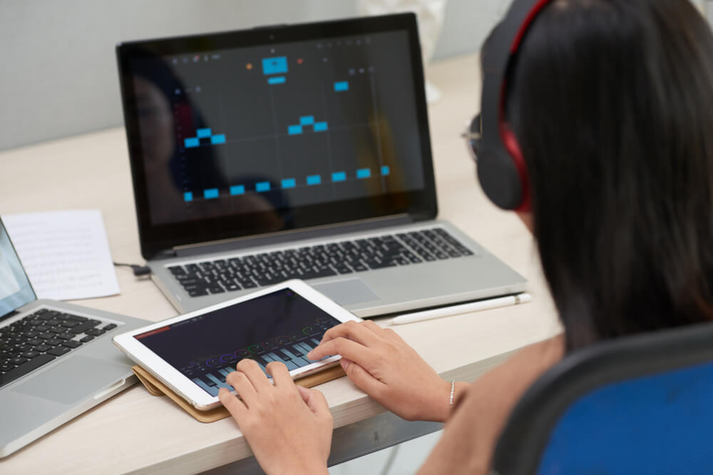 girl using a music software on tablet and laptop - music teaching apps