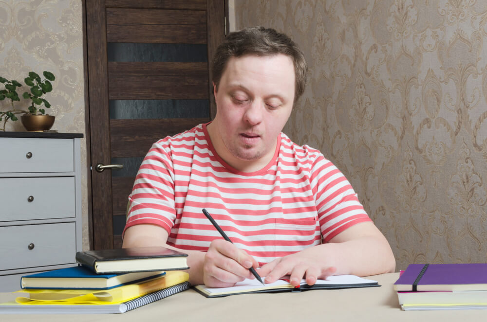 guy with disorder writing something on paper - learning disability activities at home