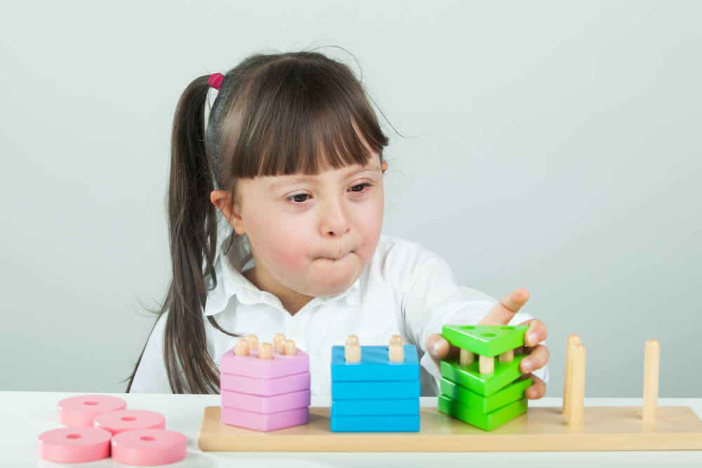 little girl playing with blocks - learning disability activities at home