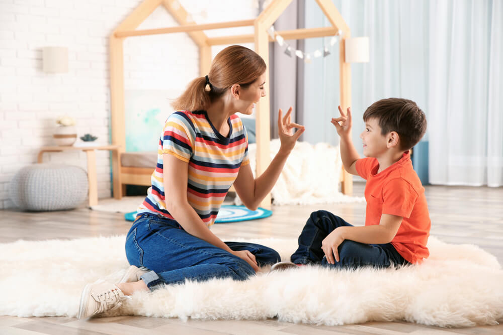 mom teaching sign langauge to son at home - learning disability activities at home