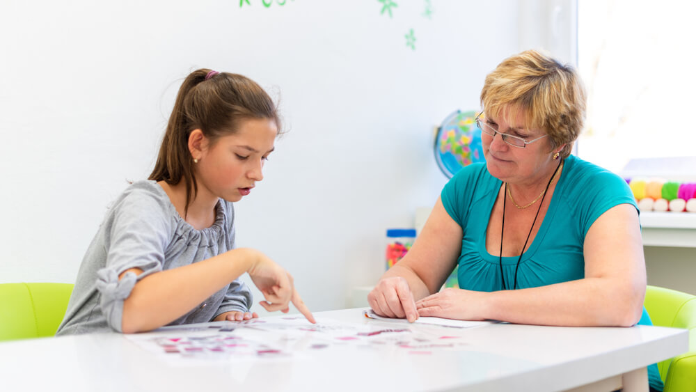 mother teaching her daughter on desk - learning disability activities at home