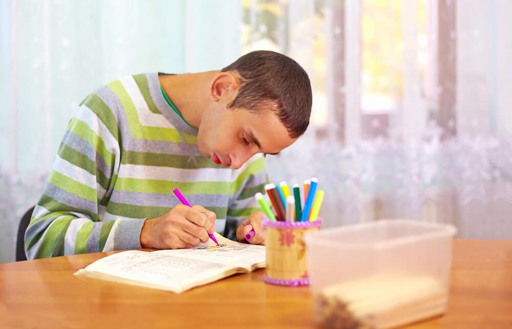 teen boy writing on a paper - learning disability activities at home