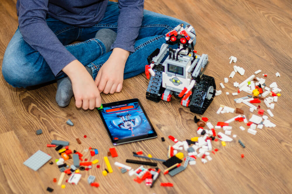 boy playing lego with his tablet and robot toy