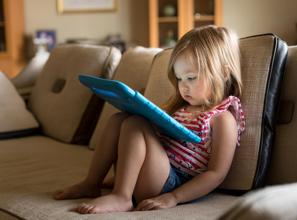 cute little girl watching video on tablet device -homeschooling toddlers