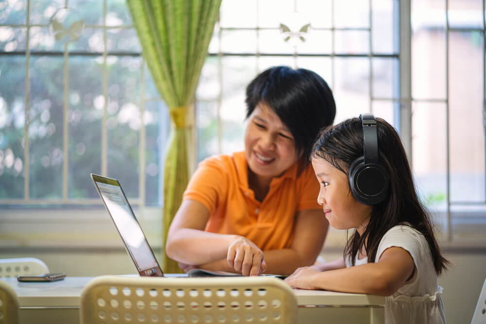 homeschooling kids - mom and daugher learning on laptop