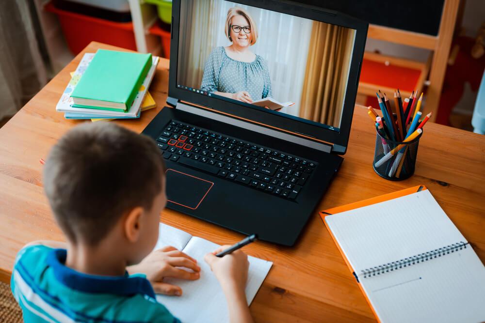 little boy watching class video of a teacher - parent engagement
