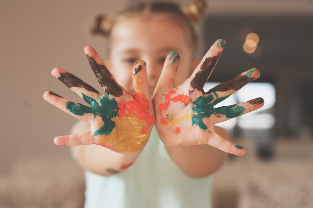 little girl opening her painted palms to the camera