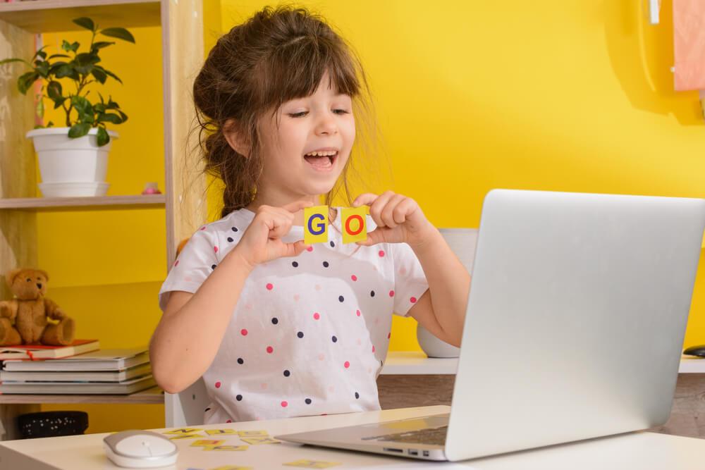 loving school - girl attending online class on a laptop - parent engagement