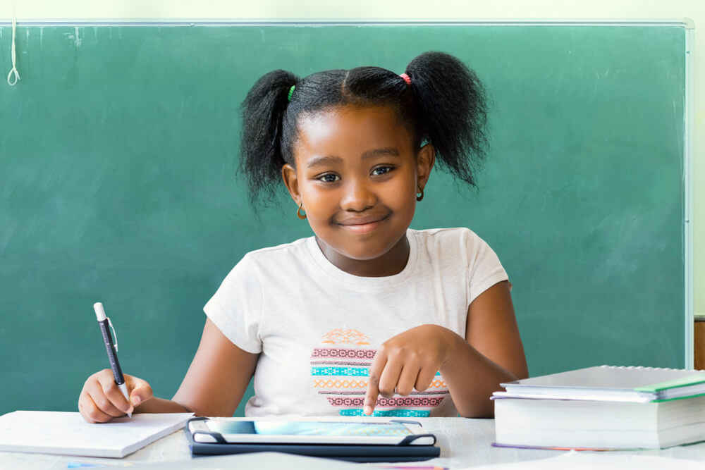 little African-American girl studying and smiling at the camera