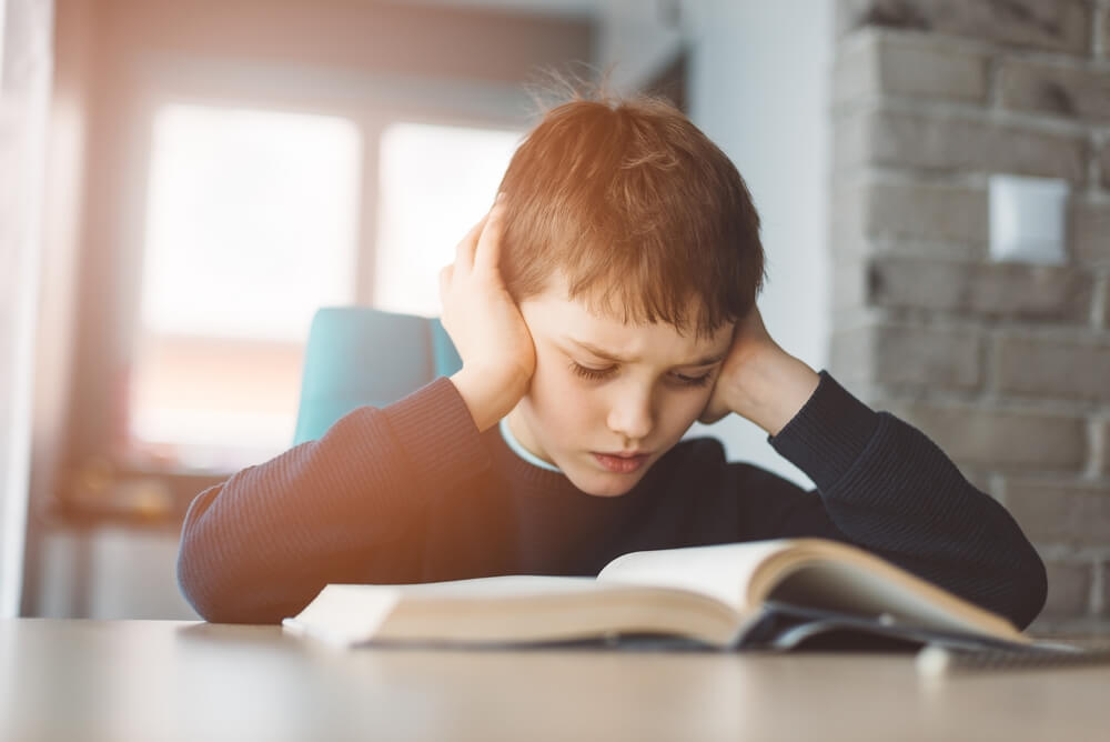 little boy studying a book and frowning