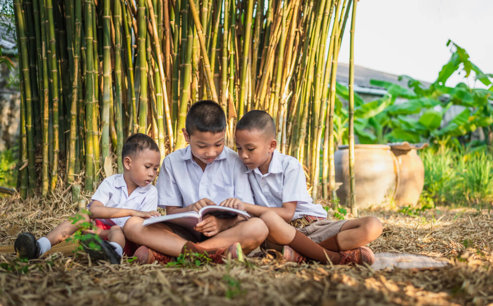 teaching with technology - three boys reading a book at the garden