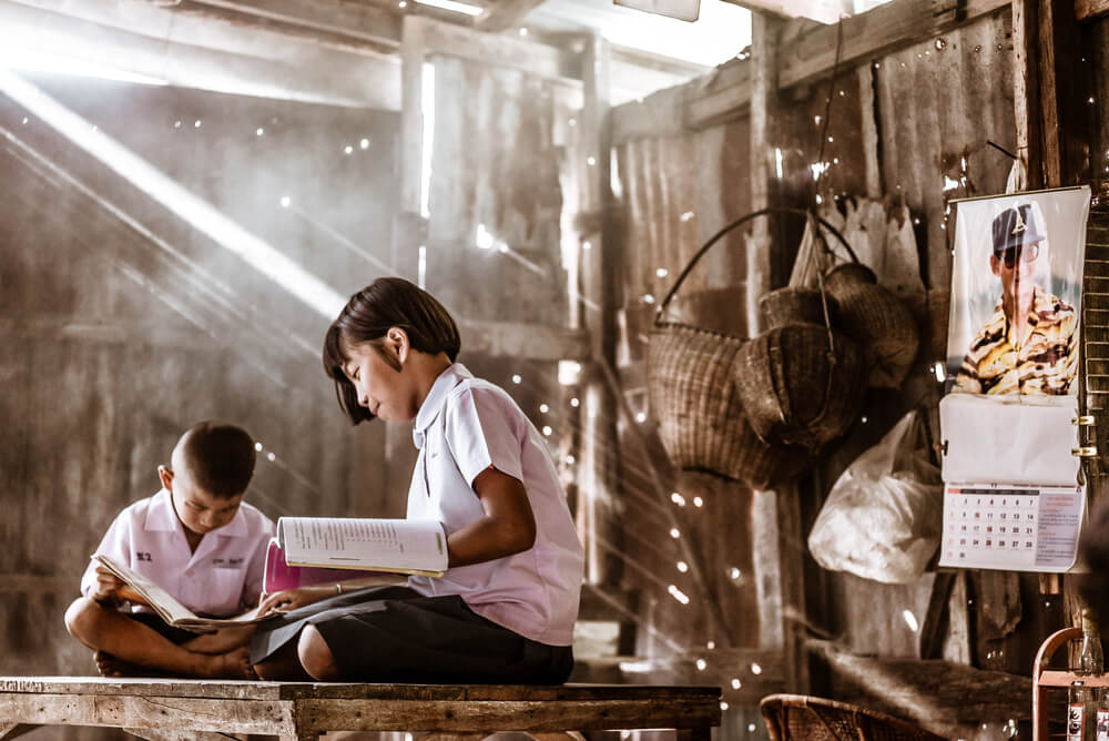 two children reading books inside a shabby hut - teaching with technology